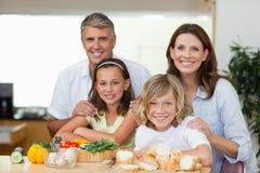 Glimlachende familie die sandwiches maakt Stock Afbeeldingen