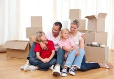 Glimlachende familie die terwijl het bewegen van huis ontspant royalty-vrije stock foto's