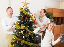 Glimlachende familie die voor Kerstmis voorbereidingen treffen Stock Afbeeldingen