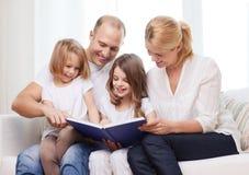 Glimlachende familie en twee meisjes met boek Stock Foto