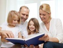 Glimlachende familie en twee meisjes met boek Royalty-vrije Stock Afbeeldingen