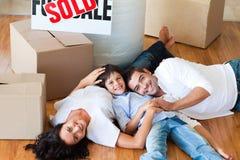 Glimlachende familie in hun nieuw huis dat op vloer ligt Stock Afbeeldingen