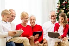 Glimlachende familie met de computers van tabletpc thuis stock foto