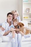Glimlachende familie met een hond Stock Afbeeldingen