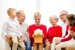Glimlachende familie met gift thuis Royalty-vrije Stock Foto