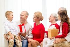 Glimlachende familie met giften thuis Stock Afbeeldingen