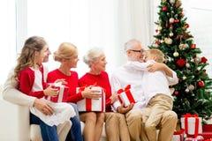 Glimlachende familie met giften thuis Stock Afbeelding