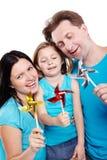 Glimlachende familie met windmolens in handen stock afbeelding