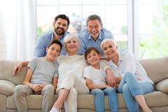 Glimlachende familie op bank Stock Afbeeldingen