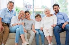 Glimlachende familie op bank Stock Fotografie