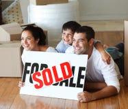 Glimlachende familie op de vloer na het kopen van huis stock afbeeldingen