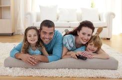 Glimlachende familie op vloer in woonkamer stock foto's