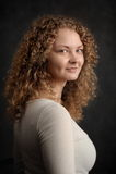 Glimlachende feevrouw met rood krullend haar, grote borst op donker grijs Stock Fotografie