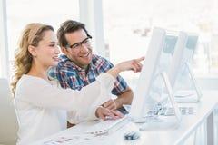 Glimlachende fotoredacteurs die computer met behulp van Stock Foto's