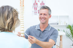 Glimlachende fysiotherapeut die stekelmodel tonen aan zijn patiënt Stock Afbeeldingen