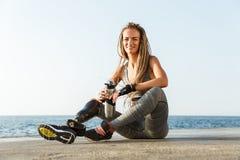 Glimlachende gehandicapte atletenvrouw met prothetisch been stock afbeeldingen