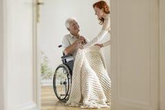 Glimlachende gehandicapte mens in de rolstoel en vriendschappelijke vrijwilliger binnen stock foto
