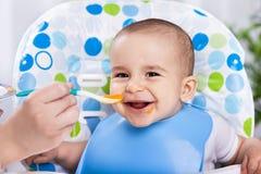 Glimlachende gelukkige aanbiddelijke baby die fruitbrij eten Royalty-vrije Stock Foto