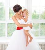 Glimlachende gelukkige bruid en een bloemmeisje binnen Stock Foto