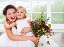 Glimlachende gelukkige bruid en een bloemmeisje binnen Royalty-vrije Stock Foto