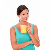 Glimlachende gelukkige donkerbruine vrouw met koffiemok Stock Afbeeldingen