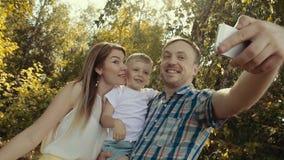 Glimlachende gelukkige familie die selfie foto in het bos nemen stock footage