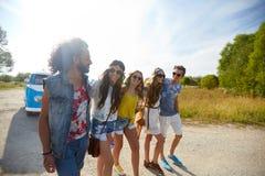 Glimlachende gelukkige jonge hippievrienden bij minivan auto Royalty-vrije Stock Foto
