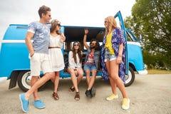 Glimlachende gelukkige jonge hippievrienden bij minivan auto Royalty-vrije Stock Foto's