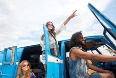 Glimlachende gelukkige jonge hippievrienden bij minivan auto Royalty-vrije Stock Afbeeldingen