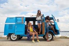 Glimlachende gelukkige jonge hippievrienden bij minivan auto Stock Foto's
