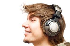 Glimlachende gelukkige jonge mens in hoofdtelefoons royalty-vrije stock fotografie