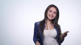 Glimlachende gelukkige jonge vrouw die aan muziek met oortelefoons en dansen luisteren geïsoleerd op witte achtergrond stock footage