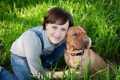 Glimlachende gelukkige jonge vrouw die in denimoverall haar rode leuke hond Shar Pei in het groene gras in park voor altijd koest Royalty-vrije Stock Fotografie