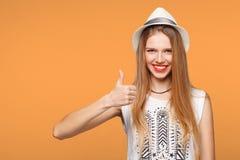Glimlachende gelukkige jonge vrouw die die duimen tonen, op oranje achtergrond worden geïsoleerd Royalty-vrije Stock Afbeelding