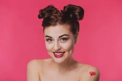 Glimlachende gelukkige jonge vrouw op een roze achtergrond Royalty-vrije Stock Afbeeldingen
