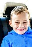 glimlachende gelukkige Jongen in de zetel van de kindauto royalty-vrije stock foto