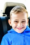glimlachende gelukkige Jongen in de zetel van de kindauto stock afbeelding