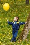 Glimlachende gelukkige jongens whith gele ballon Stock Foto