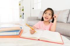 Glimlachende gelukkige meisjeskinderen die thuiswerk schrijven stock afbeeldingen