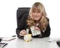 Glimlachende gelukkige onderneemster met spaarvarken royalty-vrije stock fotografie