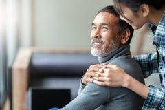 Glimlachende gelukkige oudere Aziatische vader met modieuze korte baard wat betreft dochter` s hand bij schouder het kijken royalty-vrije stock foto's