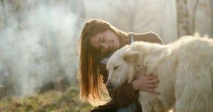 Glimlachende gelukkige vrouw die zacht witte hond strijken rond brandplaats echte vriendenmensen openlucht het kamperen tentvakan stock videobeelden