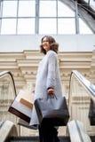 Glimlachende gelukkige vrouw in gebreide heldere de zomerlaag met het winkelen zakken op roltrap in stadswinkelcentrum royalty-vrije stock afbeeldingen