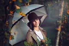 Glimlachende gelukkige vrouw onder de herfstbomen Stock Afbeeldingen