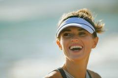 Glimlachende geschikte sportenvrouw op zeekust in avond royalty-vrije stock afbeelding
