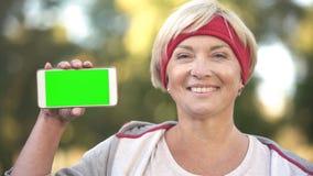 Glimlachende geschikte vrouw die op middelbare leeftijd het groene scherm mobiele telefoon, sporten app tonen royalty-vrije stock foto