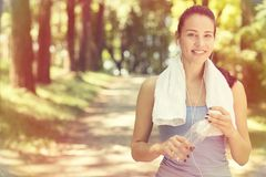 Glimlachende geschikte vrouw met witte handdoek die na sportoefeningen rusten Stock Foto