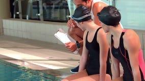 Glimlachende geschikte vrouwenzwemmers met trainer stock video