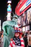 Glimlachende gezien vrouw die in een vlag van de V.S. en de hoed van de V.S. wordt gedrapeerd royalty-vrije stock afbeeldingen