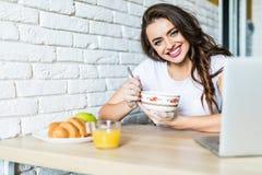 Glimlachende gezonde vrouw die cornflakesgraangewas eten terwijl het zitten van en het hebben van ontbijt bij de keukenlijst royalty-vrije stock foto's